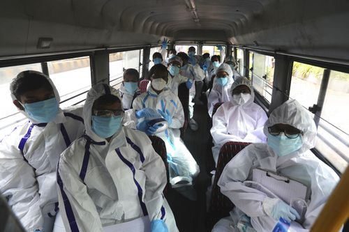 Health workers arrive on a bus to conduct a free medical checkup at residential building in Mumbai, India.