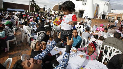 A Venezuelan migrant plays with his son during an outdoor breakfast in Bogota, Colombia.