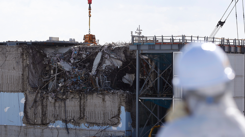 A member of the media, wearing a protective suit and a mask, looks at the No. 3 reactor building at Tokyo Electric Power Co's (TEPCO) tsunami-crippled Fukushima Daiichi nuclear power plant in Okuma town, Fukushima prefecture February 10, 2016.  REUTERS/Toru Hanai/Pool