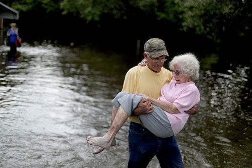 Bob Richling carries Iris Darden, 84, out of her flooded home in Spring Lake, North Carolina.
