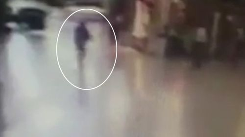 The terrorist is seen running through the terminal holding an AK-47