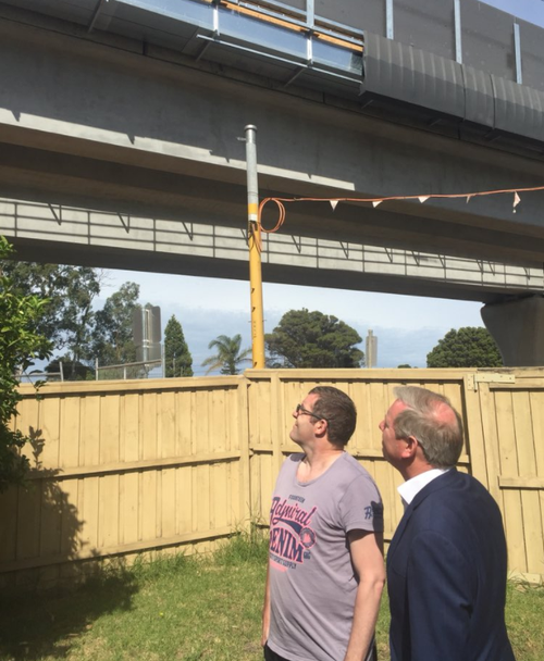 Noble Park resident Chris Papapavlou looks up at the SkyRail project hovering over his backyard. (Dougal Beatty / 9NEWS)