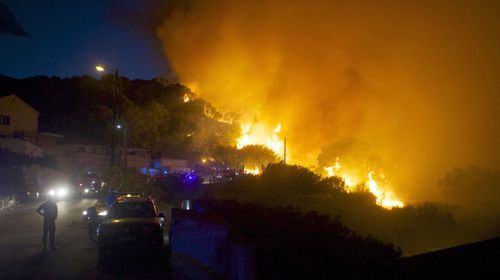 firefighters work to stop a forest fire on a hillside near the village of Ortale, Corsica island, France. (AAP)