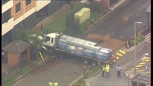 An aerial view of the truck which pinned a car close to the wall of a unit block.