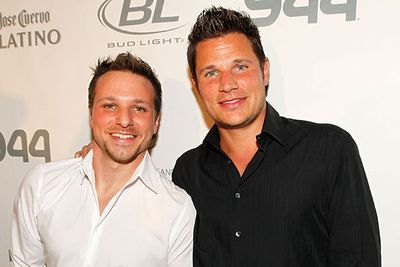 He's smiling bravely, but you just know Drew Lachey is secretly wishing he'd brought a box to stand on before posing next to hotter brother Nick in this photo…