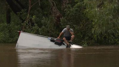 Driver takes refuge on top of car after driving into floodwaters