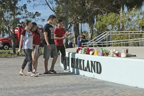 Students place flowers on the stage outside the Pines Trail Center in Parkland. Picture: AAP