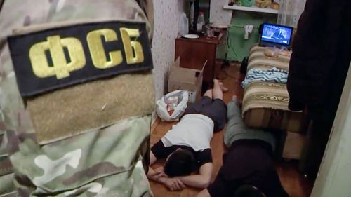 Russian Federal Security Service (FSB) operatives detain a suspected member of the Islamic State group's cell in St. Petersburg, Russia (Russian Federal Security Service video via AP)