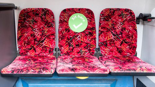 Green stickers show where people can sit on the bus.