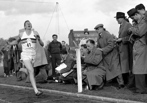 Sir Roger Bannister hits the tape to become the first person to break the four-minute mile in Oxford, England. (AAP)