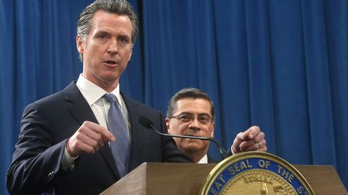 California Gov.ernor Gavin Newsom, left, flanked by Attorney General Xavier Becerra,