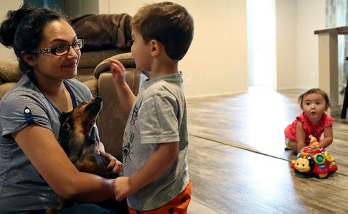 Danielle Shields, the widow of Devin Patrick Kelley, plays with their children, Michael, and Raeleigh, at her home at her home in Cibolo, Texas.