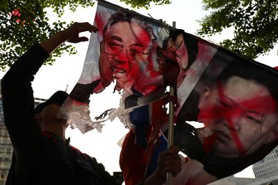 Protesters in Seoul, the capital of South Korea – burnt flags of Kim Jong-Un showing a joint stance against the imminent meeting