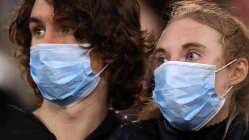 Spectators look on wearing face masks during the round 7 AFL match between the Geelong Cats and the Collingwood Magpies