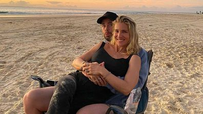 Liam Hemsworth and Elsa Pataky cuddle on the beach.