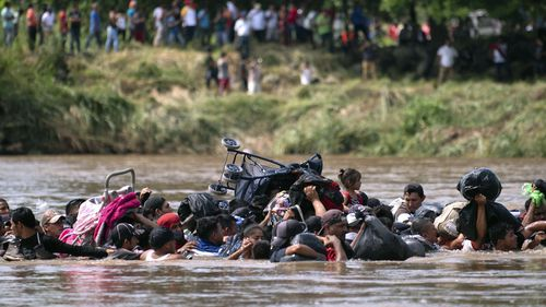 A new group of Central American migrants wade in mass across the Suchiate River, that connects Guatemala and Mexico, in Tecun Uman, Guatemala.