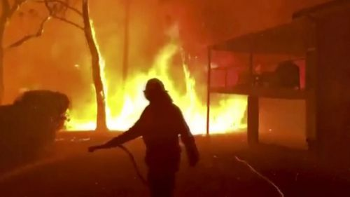 A firefighter sprays water on a fire moving closer to a home in Blackheath, New South Wales.