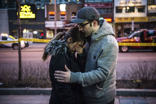 Farzad Salehi consoles his wife, Mehrsa Marjani, who was at a nearby cafe and witnessed the carnage. Picture: AP/The Canadian Press
