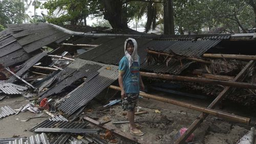 A man inspects his house which was damaged by a tsunami, in Carita, Indonesia.