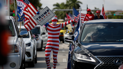 A man wearing a flag-themed body stocking walks between lines of cars as hundreds of vehicles gather for a car caravan in support of President Donald Trump, at Tropical Park in Miami, Sunday, Nov. 1, 2020. (AP Photo/Rebecca Blackwell)