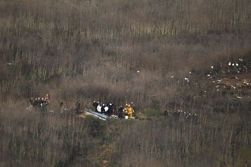 A body is removed from the scene of a helicopter crash that killed former NBA basketball player Kobe Bryant