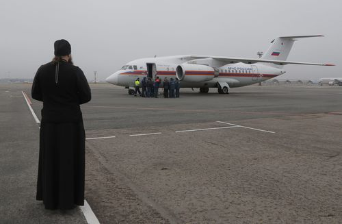 An Orthodox priest looks on as a Russian Ministry for Emergency Situations plane carrying bodies of victims of the Russian plane crash in Egypt, at Pulkovo airport outside St. Petersburg, Russia, 06 November 2015. All 224 people onboard a Russian MetroJet Airbus A321 plane en route from the Red Sea resort of Sharm el-Sheikh to Russian St. Petersburg were killed in the crash on 31 October 2015. British security experts believe a bomb placed in the plane's hold caused the crash of the Russian passenger jet in Egypt's Sinai Peninsula, the BBC and other media said 06 November. EPA/DMITRY LOVETSKY / POOL