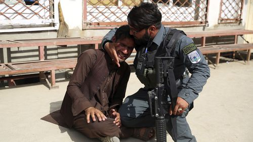 An Afghanistan police officer comforts a grieving man after a terrorist attack on a maternity hospital in Kabul.