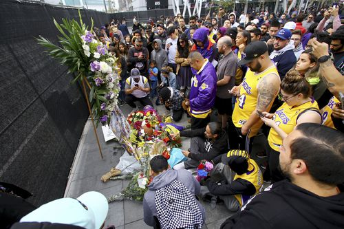 Fans of Kobe Bryant mourn at a memorial to him in front of Staples Center, home of the Los Angeles Lakers, after word of the Lakers star's death in a helicopter crash.
