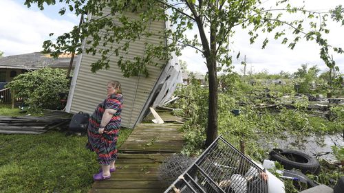 Angel Funk stands in the backyard of her Franklin, Texas, home following severe weather. Funk's home was struck by her neighbour's mobile home, but she and her husband, who were home at the time, escaped unharmed.