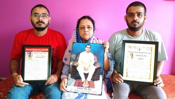 Anindita Mitra, 61, flanked by her sons Satyajit Mitra, right and Abhijit Mitra, pose with portraits of her husband late Narayan Mitra.