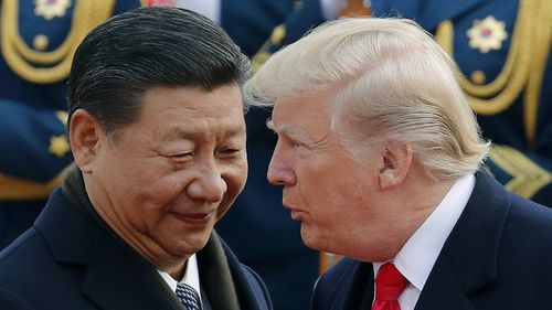US President Donald Trump chats with Chinese President Xi Jinping during a welcome ceremony at the Great Hall of the People in Beijing. The United States and China are scheduled to resume talks today to try to back off an escalating trade war.