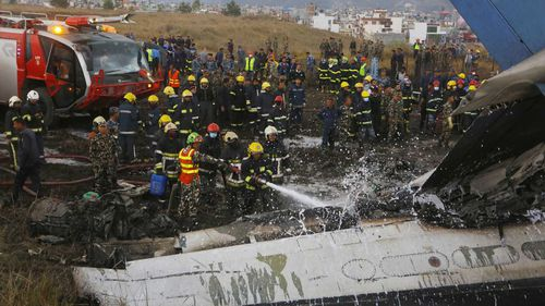 Firefighters douse the wreckage of a crashed plane in Kathmandu. (AAP)