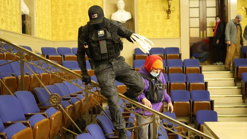 A protester spotted inside the Senate chamber carrying plastic zip-tie handcuffs has prompted theories some in the Capitol riot wanted to catch and detain hostages.