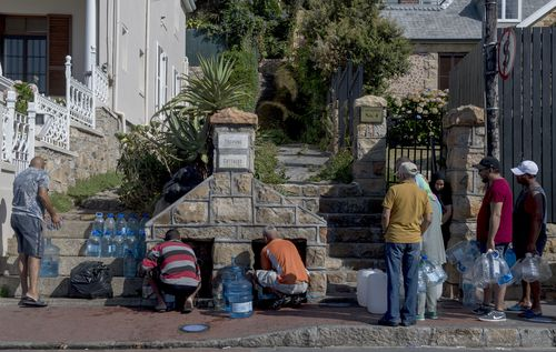 People queue to collect water from a natural spring in the Cape Town, South Africa. (AAP)