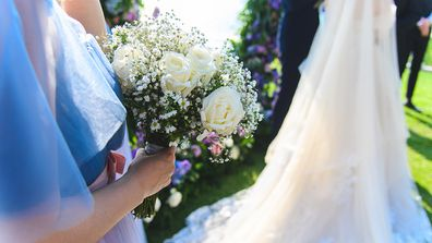 Bridal bouquet in the bridesmaid hand at the wedding ceremony