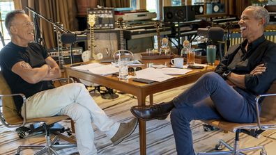 Bruce Springsteen, left, appears with former President Barack Obama during their podcast of conversations recorded at Springsteen's home studio in New Jersey. The eight-episode series covers their upbringings, racism, fatherhood and even recall a White House singalong around a piano.