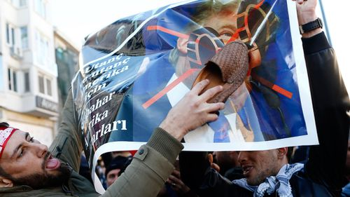 Protesters deface a poster with Donald Trump's face on it. (AAP)