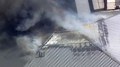 Fire is tearing through the roof of the property. (9NEWS)