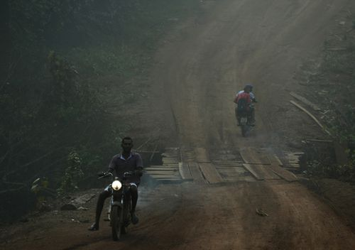 Residents motorcycle amid smoke from forest fires at dawn in the Vila Nova Samuel region, along the road to the National Forest of Jacunda, near the city of Porto Velho. Experts from the country's satellite monitoring agency say most of the fires are set by farmers or ranchers clearing existing farmland, but the same monitoring agency has reported a sharp increase in deforestation this year as well.