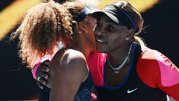 Naomi Osaka is embraced by Serena Williams.