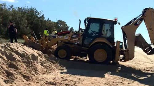 An excavator has been called in to help free the man. Picture: 9NEWS