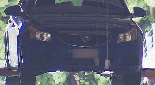 The dark sedan undergoing forensic testing.