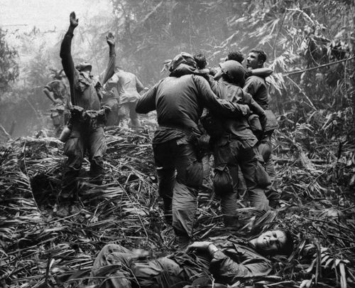 As US troopers aid wounded comrades, the first sergeant of A Company, 101st Airborne Division, guides a helicopter through the jungle foliage to pick up casualties suffered during a five-day patrol near Hue, April 1968.