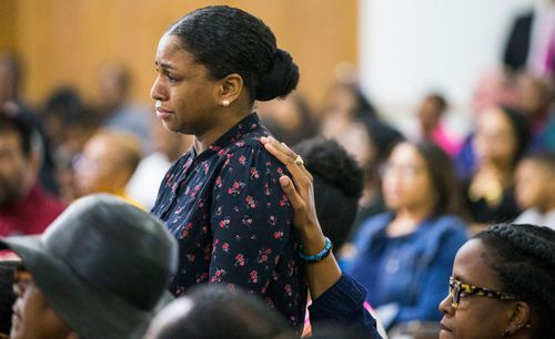 Cynthia Johnson, Botham Jean's girlfriend, stands up as she is comforted by another churchgoer during a prayer service,