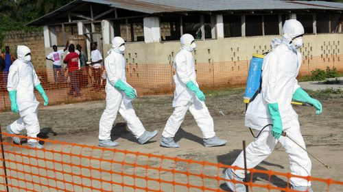 Liberian health workers in protective gear on the way to bury a woman who died of the Ebola virus in Liberia. (AP)