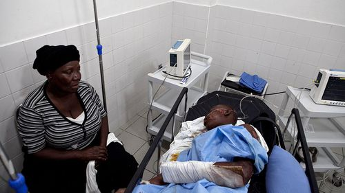 man injured in a bus crash is accompanied by his relatives at the hospital of Gonaives. (AAP)