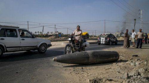 Palestinian onlookers and motorists pause to inspect an Israeli army bomb laying unexploded on the road, prior to the truce being broken. (Getty Images)