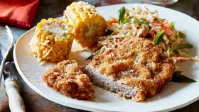 Rosemary beef schnitzel with coleslaw and corn