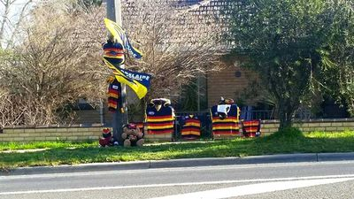"""The colours red, gold and navy blue are emblazoned across social media today as fans pay tribute to late Adelaide Crows coach Phil Walsh by hanging their scarves and guernseys outside their homes.<br _tmplitem=""""84""""> <br _tmplitem=""""84"""">Walsh was found stabbed to death in his Adelaide home in the early hours of this morning. His son has been charged with his murder.<br _tmplitem=""""84""""> <br _tmplitem=""""84"""">Twitter has been flooded with tributes to Walsh featuring the club's motto #weflyasone as the tag.<br _tmplitem=""""84""""> <br _tmplitem=""""84"""">This tribute was spotted in Bendigo, Victoria and posted to Facebook by Becci Brown.<br _tmplitem=""""84"""">"""