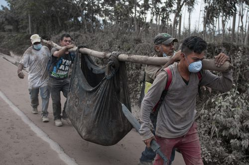 Rescue workers carry away the bodies of victims from the volcano. Picture: AAP